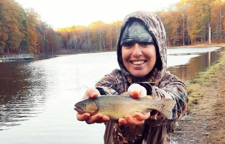 angler gabriella hoffman holding a rainbow trout she caught at locust shade park