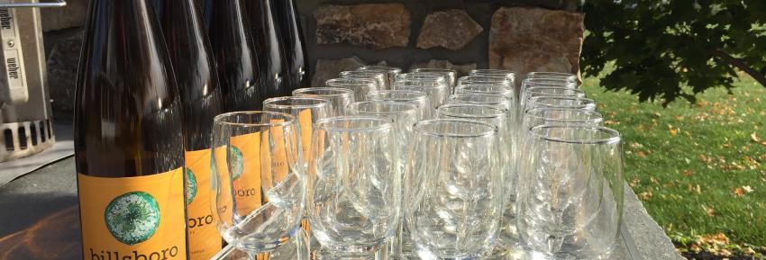 Bottles sit outside next to unused crystal glasses at Billsoboro Winery on Seneca Lake