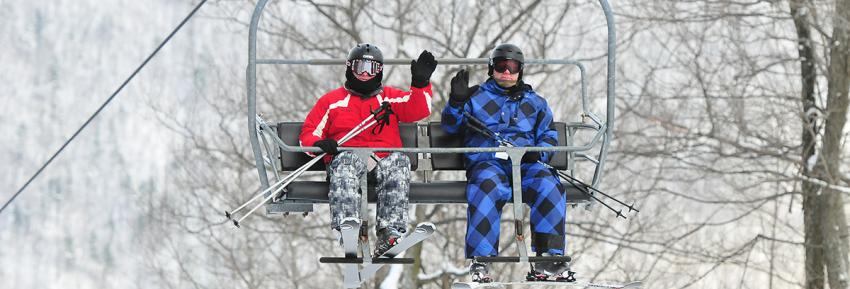 Two skiers wave to the camera from the chairlift at Bristol Mountain Ski Resort