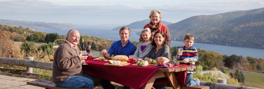 A family smiles for the camera while picnicking at the Coutny Road 12 Scenic Overlook