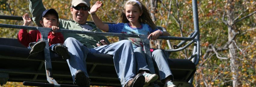 A family waves from the chairlift during a fall sky ride at Bristol Mountain