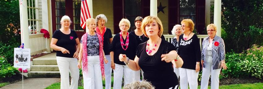 A group of women sing inside of Sonnenberg Gardens and Mansion
