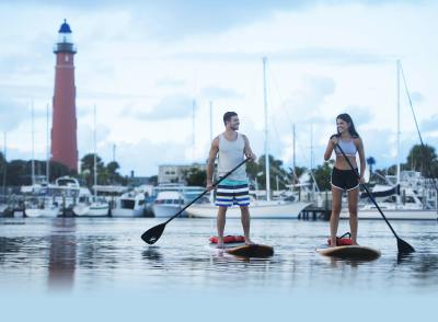 Paddleboarding Couple by Lighthouse