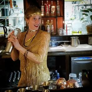 a woman dressed as a 1920's Flapper tending bar at a tasting room