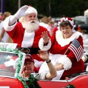 Mr and Mrs Santa Claus waving to a crowd from a vehicle in a parade