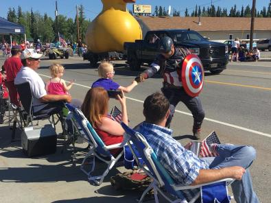 Man dressed in Captain America costume shaking hands with a young parade spectator
