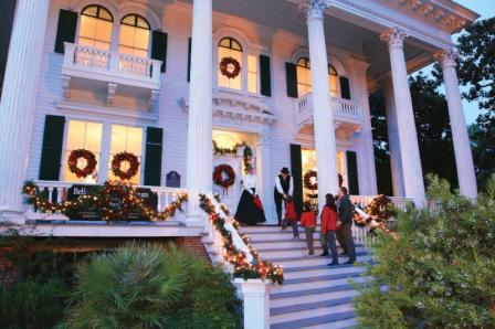 Family walking up the steps at Bellamy Mansion at Christmas