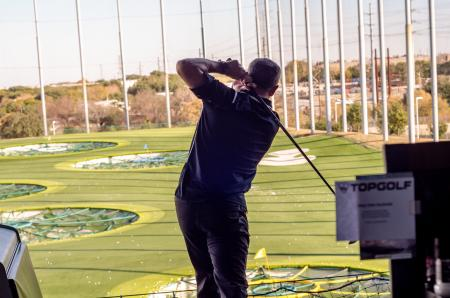 Man swinging club at topgolf during Thanks FORE Giving Golf Tournament hosted by the Visit Austin Foundation