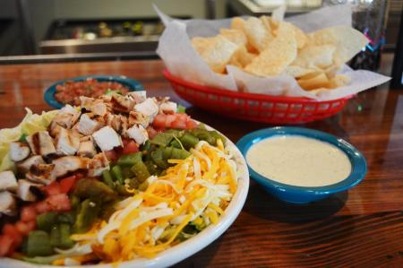 chuys florence ky creamy jalapeno dip, chips, plate of mexican food showcased on a bar