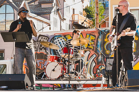 Singer, Guitarist, and Drummer on outdoor stage