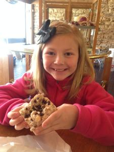 A girl holding up a sweet treat at Hazel Hill in Kansas