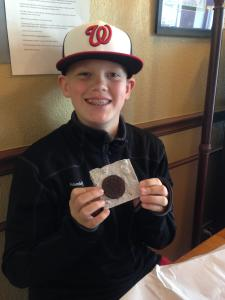 A boy holding up a chocolate treat at Hazel Hill in Kansas