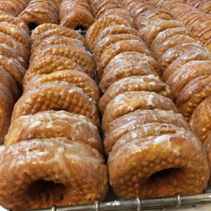 Dozens of glazed pumpkin donuts in rows