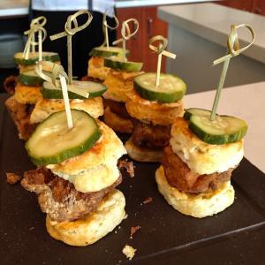 Mini slider burgers topped with pickle garnish at Taste of Dine Originals