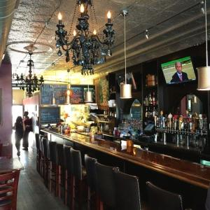 View inside antique wood countertops, chandeliers and bar inside The Olde Towne Tavern