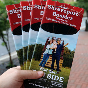 person holding four Shreveport-Bossier visitor guides