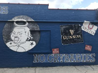 "The ""No crybabies"" mural on the side of Five Points Bottle Shop."
