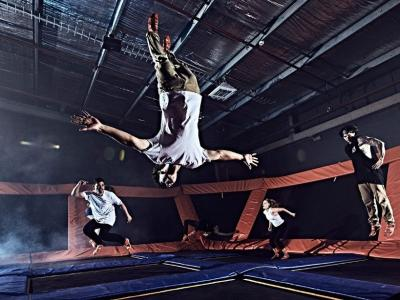 People jumping and flipping on trampolines inside Sky Zone