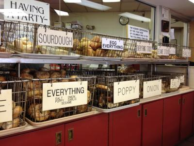 Shelf stocked with baskets full of various flavors of bagels at Blocks Bagels