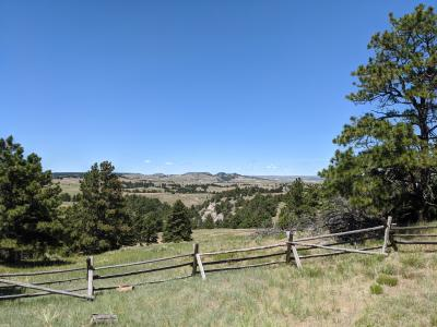 A log fence overooks rolling hills and mountain ranges as the land slopes down into canyons and hills outside Albin, Wyoming, used for cattle pasture land.