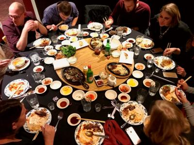 Table surrounded by diners and completely covered in various Korean dishes and saucebowls