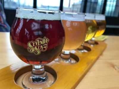 Flight of colorful beers in snifters marked with the Seventh Son Brewing logo