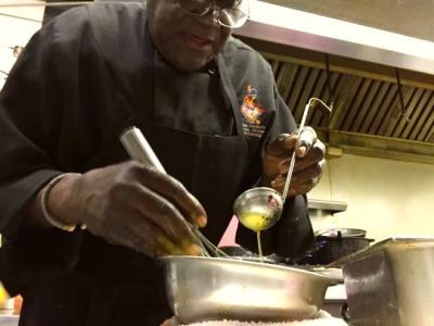 Chef cooking sauce in kitchen of Creole Kitchen restaurant