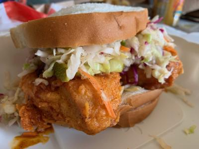 Sandwich topped with fried chicken and cole slaw from Hot Chicken Takeover