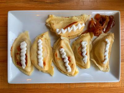 Pierogis topped with sauce on white plate from Pierogi Mountain