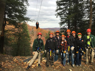 A group of zipliners pose for a photo in the trees at Bristol Mountain Aerial Adventures