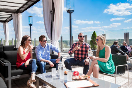 Two couples enjoying cocktails on the rooftop patio at VASO