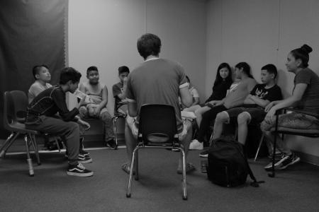 Black & white image of children seated in circle during songwriting workshop with We Amplify Voices