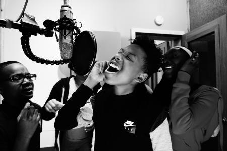 Black & white photo of children singing into microphone in recording studio booth