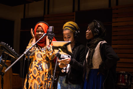 Diverse students standing at microphone in recording studio as a part of the We Amplify Voices program