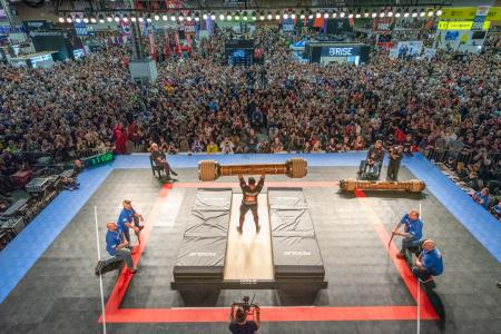 View from above and behind of bodybuilder lifting massive barbell in front of crowded audience at The Arnold Sports Festival