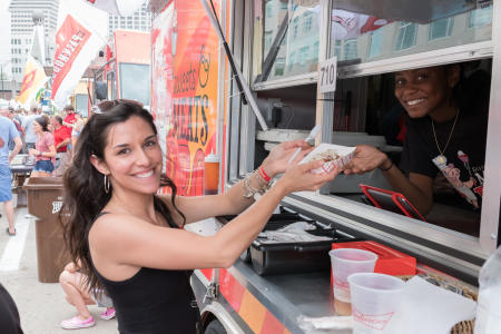 woman receiving a boat of food from a food truck during taste of cincinnati at fountain square