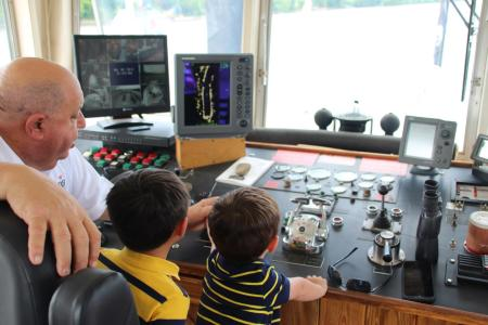 riverboat captain and two children at the controls of the vessel during bb riverboat cruise on the ohio river