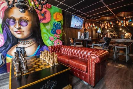 artwork on wall near bar of sugar whiskey sis moonsine bar in covington ky with chess board on coffee table and large red leather couch
