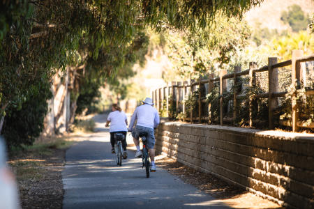 two people riding bikes along a paved path