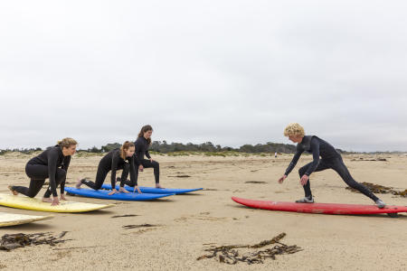 Central Coast Surf School teaching group how to stand on surf boards