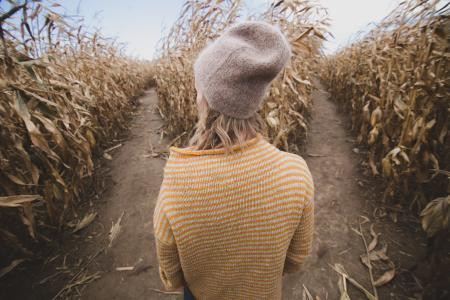 woman standing in brown corn maze looking sideways