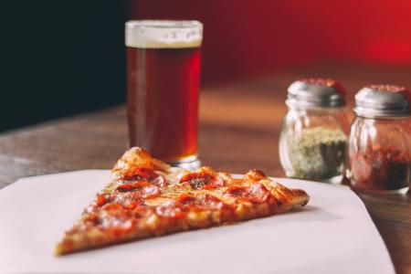 Slice of pepperoni pizza with a beer