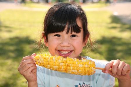 girl holding an ear of corn