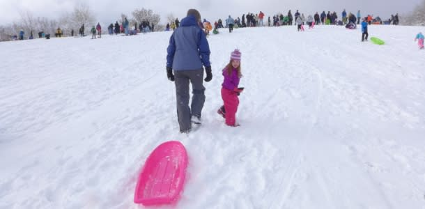 Adults and Kids sledding at Scott Carpenter Park Boulder