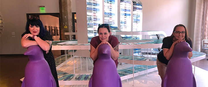 Women at 21c posing with purple penguins