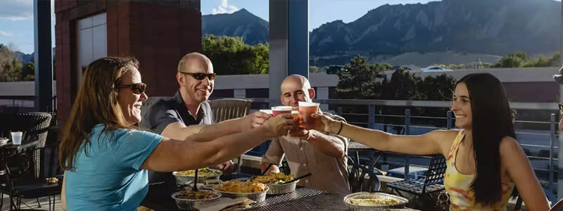 Two men and two women raising glasses to cheers on an outdoor patio