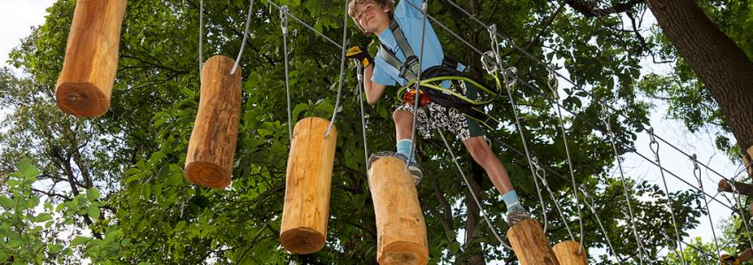 A kid crosses the obstacle course in the trees at Bristol Mountain Aerial Adventures