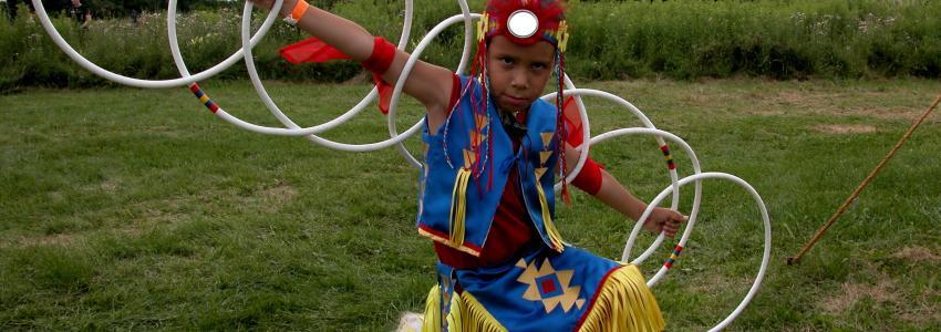 A boy poses with rings around him at Ganondagan