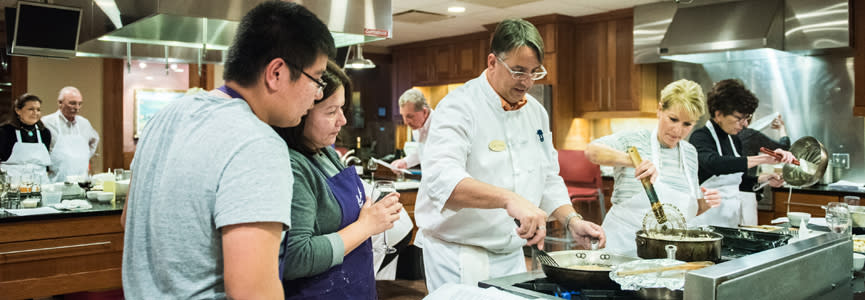 Pairs of people get a hands on cooking experience with a professional chef in the New York Wine and Culinary Center's state-of-the-art kitchen.