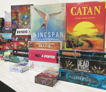 A stack of board games inside of Noble Knight Games
